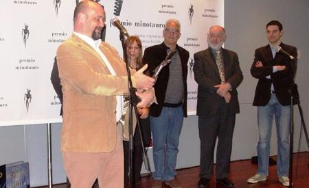 Carlos Sisí admirando su Premio Minotauro 2013, al fondo algunos miembros del jurado